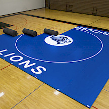 Full 42' x 42' Wrestling Mat partially set up inside a gym.